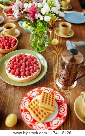 High-angle view of freshly baked raspberry tart, homemade waffles, summer flowers, French press and tea cups placed on wooden table