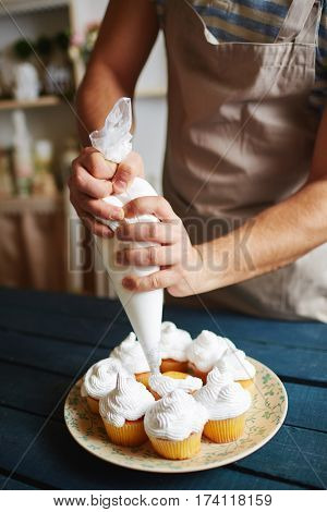 Closeup of unrecognizable man working in rustic kitchen, putting finishing touches on  freshly baked muffins with white cream using icing bag