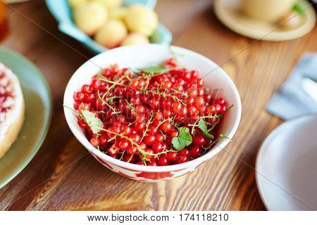 Close-up view of freshly collected ripe redcurrant lying in plate on wooden table