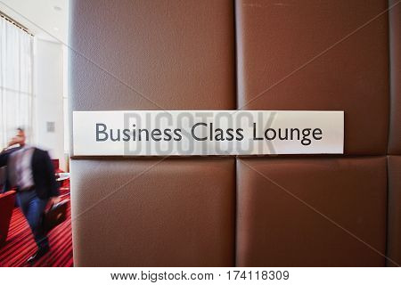 Front view of metal door sign Business Class Lounge on leather bound wall in modern airport with unrecognizable traveler passing by it