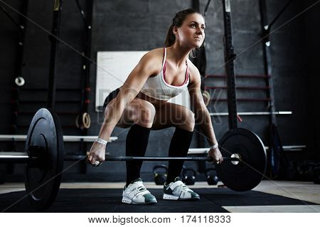 Low angle view of muscular female athlete lifting heavy barbell from floor straining with effort during working out in gym
