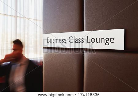 Metal door sign Business Class Lounge on leather bound wall in modern airport with unrecognizable traveler passing by it