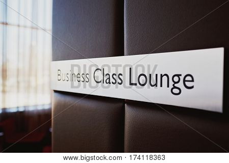 Closeup shot of  metal door sign Business Class Lounge on leather bound wall in modern airport