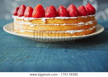 Side view of simple biscuit naked cake decorated with fresh ripe strawberries on top and white icing between layers standing on rustic wooden table