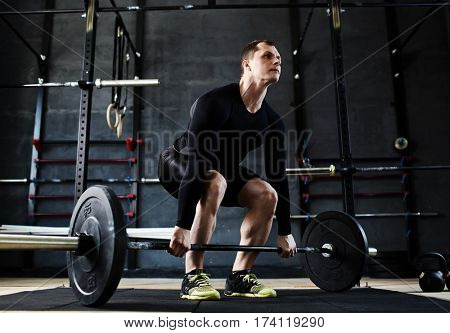 Low angle view of muscular male athlete lifting heavy barbell from floor straining with effort during working out in gym