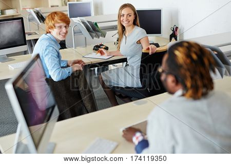 Project discussion in open plan office: young smiling businesswoman and red-haired businessman turned to their Afro-American colleague and listening to him with smile