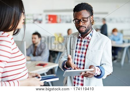 Concentrated Afro-American businessman in eyeglasses holding digital tablet in hand and pointing at something on its screen, his female colleague listening to him with attention