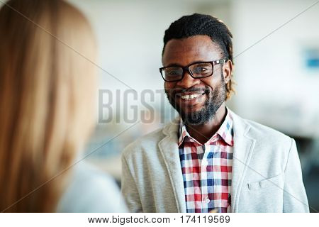 Head and shoulders portrait of cheerful bearded businessman in casualwear having conversation with his female colleague, blurred background
