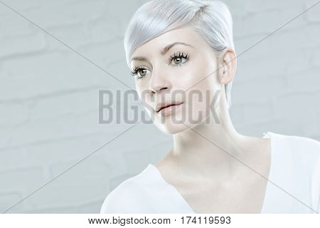 Portrait of young daydreaming woman with short platinum blonde hair.