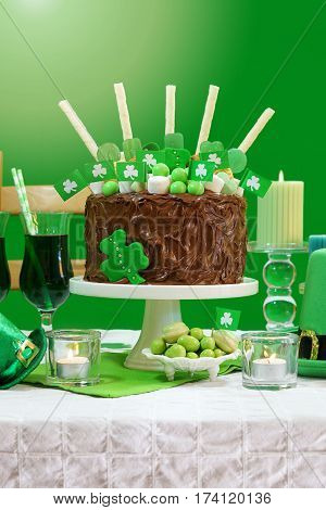 Happy St Patricks Day March 17 green and white party table with showstopper chocolate cake decorated with candy cookies and shamrock flags.