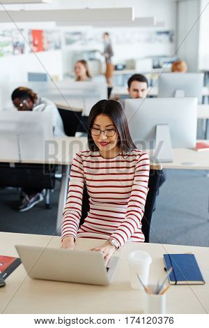 Pretty Asian woman in striped dress sitting at office desk and checking e-mails on laptop, her coworkers wrapped up in work