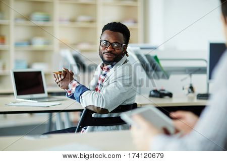 Waist-up portrait of smiling bearded man sitting at desk in open plan office and asking his colleague for advice