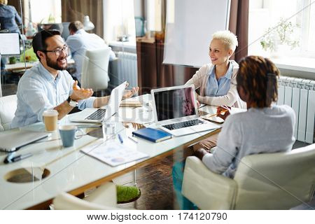 Multi-ethnic group of two businesspeople and one businesswoman sitting at table in meeting room and discussing details of their new project, modern office observed through glass wall