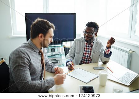 Afro-American businessman in eyeglasses sitting at wooden table and discussing new contract terms with his partner before signing it