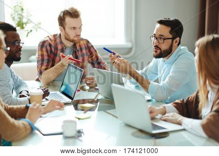 Multi-ethnic team of ambitious designers in casualwear suggesting ideas concerning their new project while sitting together in boardroom