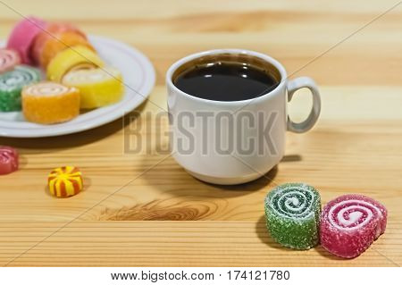 Fruit jelly and a cup of coffee on a gray wooden table. Bright colors. Coffee pause.