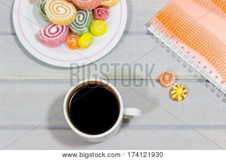 Fruit jelly and a cup of coffee on a gray wooden table. Notebook on the background. Bright colors. Coffee pause.