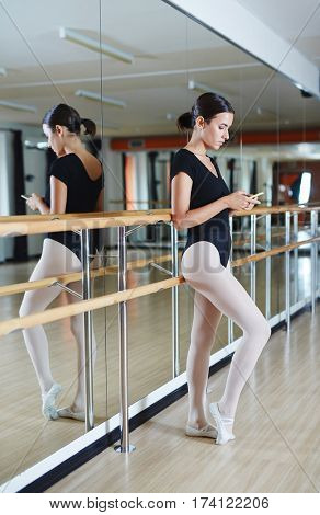Young woman in black leotard standing leaning against bar with smartphone and typing messages at break from lesson in spacious ballet studio