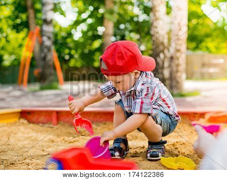 child playing in the sandbox with toy car