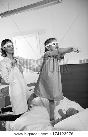Black and white photo of little girl superhero playing with doctor in hospital