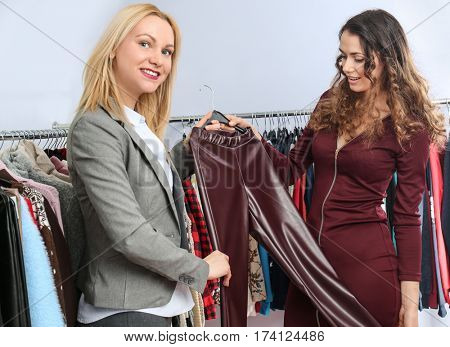 Seller helping young woman to choose clothes in modern shop