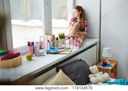 Red-haired pretty girl sitting on window sill in her bedroom, holding pencil with notepad and looking at window pensively