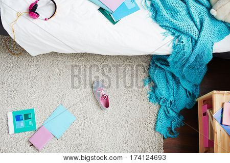Directly above view of messy room of school girl with sneakers, books and knitted blanket lying on carpet