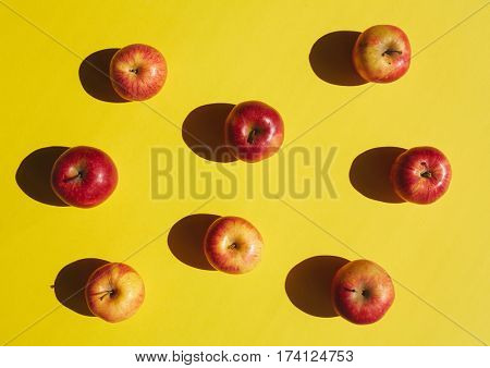 Above view of ripe red apples arranged in rows on bright yellow background, color surge concept
