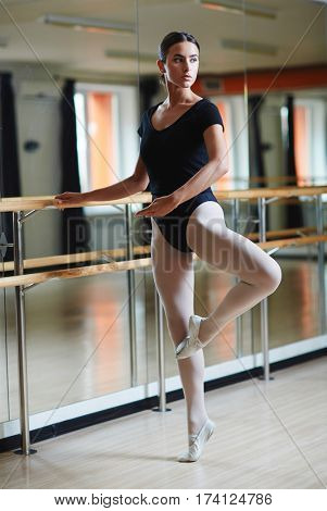 Full body shot of beautiful ballerina standing practicing moves against bar during ballet class in half-lit dance studio