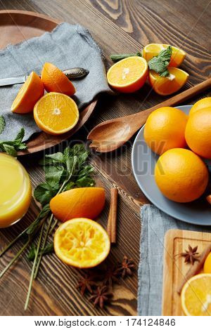 Rustic kitchen table with homegrown fruits and spices laid out on it :refreshing ripe oranges cut in half, mint, cinnamon and star anise scattered in elegant assortment round wooden cutlery