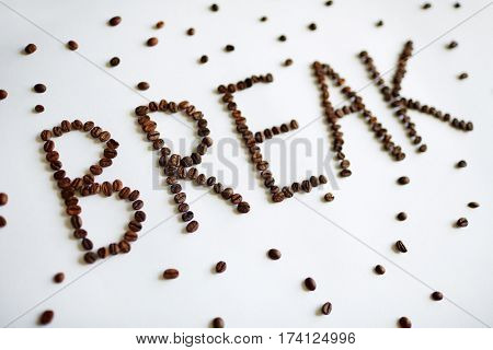 Creative coffee break concept: Word Break laid out on white table with rich roasted coffee beans in large letters with separate seeds scattered around on white table