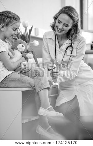 side view of smiling doctor examining girl with reflex hammer black and white photo