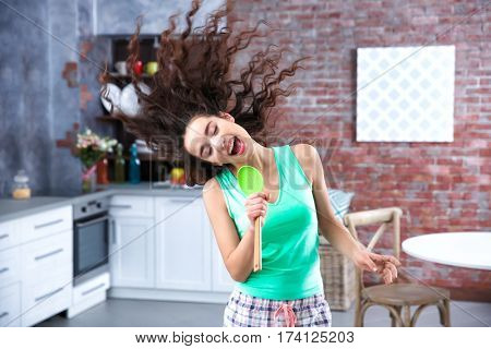 Beautiful young woman using skimmer as microphone in modern room interior