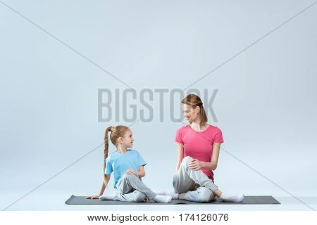 Smiling sporty mother and daughter practicing gomukhasana yoga pose on white