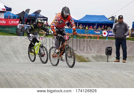 GRAVESEND, UK - APRIL 12: Riders competing in the mens class of the UK National BMX champs at the Kent cyclopark negotiate the rollers section during a heat race on April 12, 2014 in Gravesend