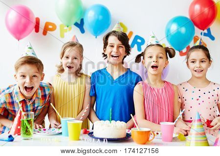 Portrait of five joyous children posing at birthday table with cake on it, smiling and showing their teeth with mouth open