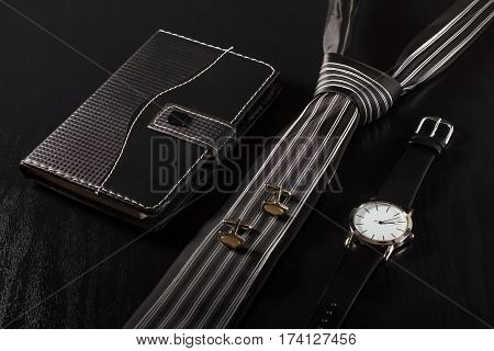 Notebook in leather cover tie cufflinks watch with a leather strap on a black background