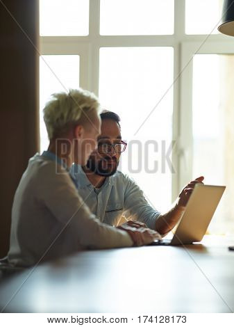 Portrait of two colleagues sitting together at table in sunlit room, both looking at laptop screen and discussing work issues, man explaining plans to woman