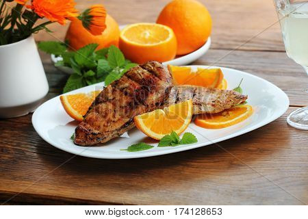 Grilled chicken breast with orange on wooden table