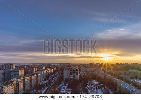 Aerial panoramic evening cityscape from rooftop of Voronezh. Houses, sunset, sky, clouds, dramatic view in warm tones with copyspace
