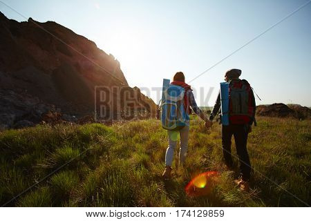 Rear view image with lens flare: young tourist couple traveling with big backpacks in nature, holding hands while walking by mountain path at sunset
