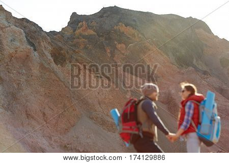 Couple of young travelers hiking in wild nature, man and woman wearing tourist gear with big backpacks standing holding hands against backgrounds of enormous mountain