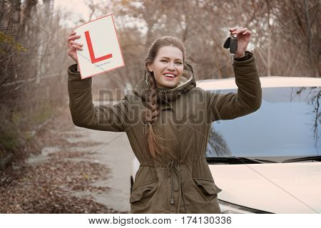 Happy young woman with learner driver sign standing near car outdoors