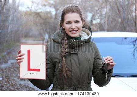 Happy young woman with learner driver sign and car key outdoors