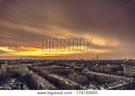 Aerial evening cityscape from rooftop of Voronezh. Houses, sunset, sky, clouds, dramatic view in warm tones