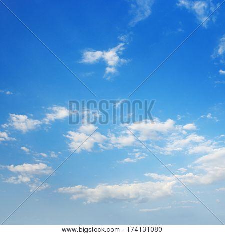 White cirrus clouds against a blue sky.