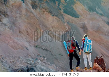 Wide shot copy space image of small figures of two people in hiking gear with tourist backpacks  standing against background of enormous mountain holding hands, rear view