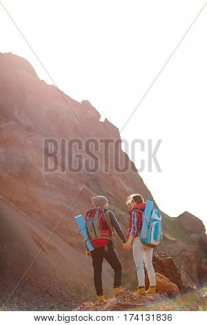 Wide shot sunlit image of two people in hiking gear with tourist backpacks standing against background of enormous mountain holding hands, rear view