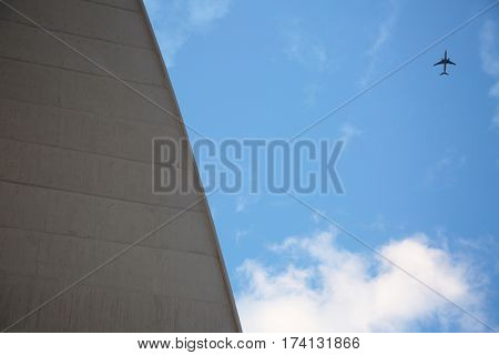 Massive building and small figure of plane flying high in blue sky, view from below