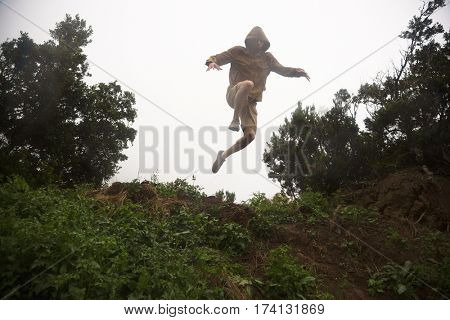 Young fearless hiker in hood and jacket jumping off the green hill, view from below
